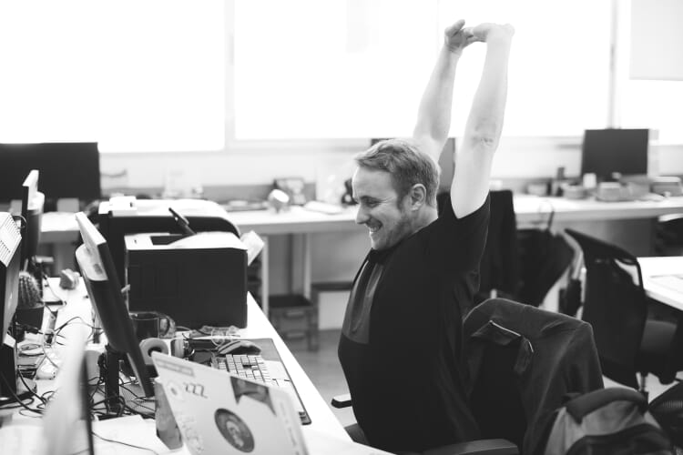 Man Stretching Arms during Break Time at Office